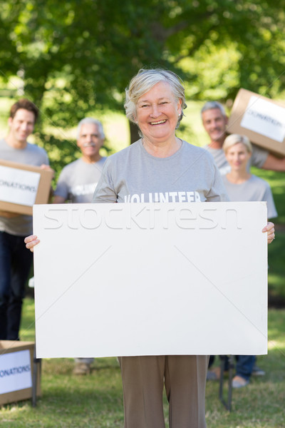 Happy volunteer grandmother holding blank Stock photo © wavebreak_media
