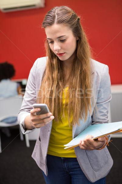 Casual businesswoman text messaging in office Stock photo © wavebreak_media