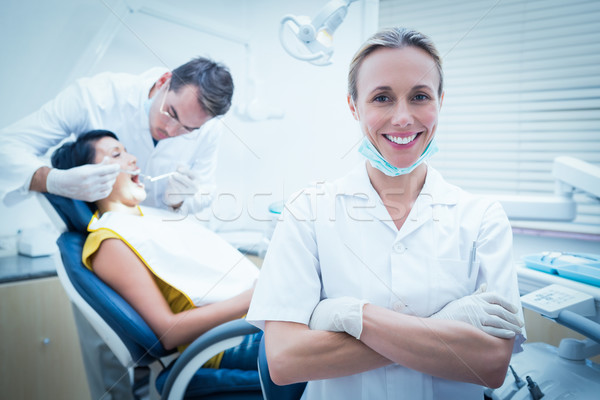 Smiling female dentist with assistant examining womans teeth Stock photo © wavebreak_media