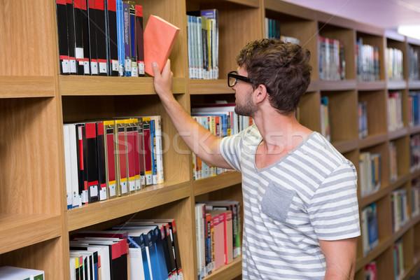 Estudante livro prateleira biblioteca universidade Foto stock © wavebreak_media