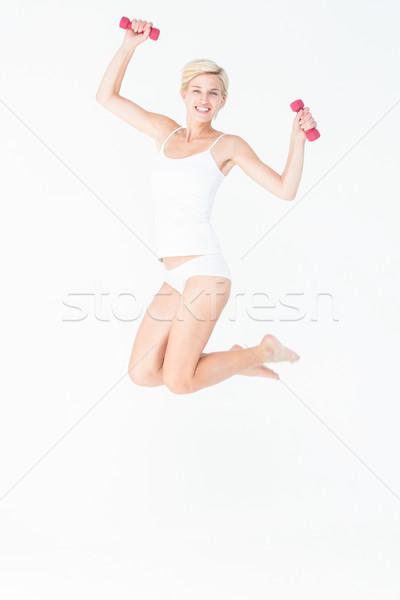 счастливым женщину прыжки гантели белый Сток-фото © wavebreak_media