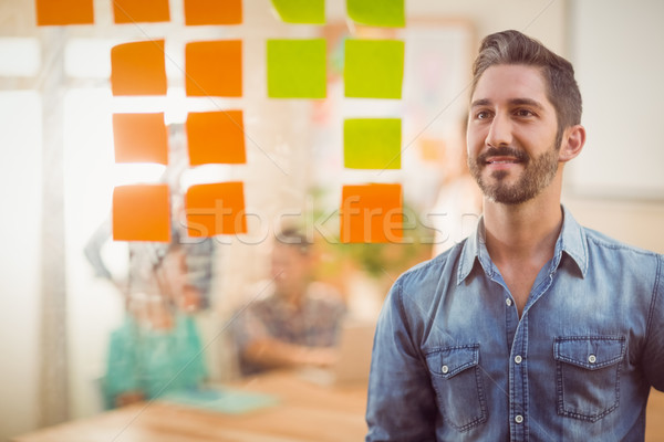 Happy businessman looking post its on the wall Stock photo © wavebreak_media