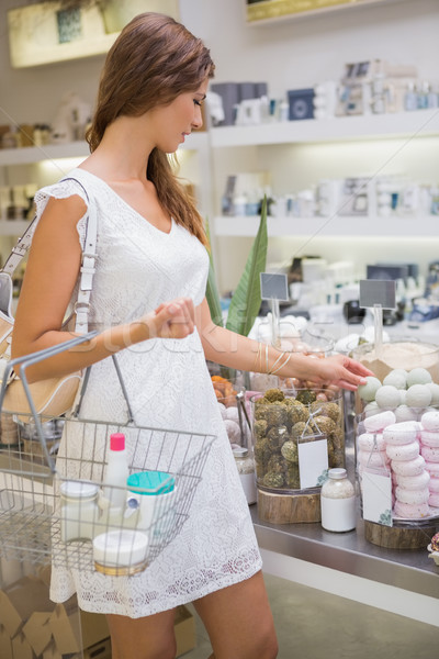 Woman with shopping basket testing soap Stock photo © wavebreak_media