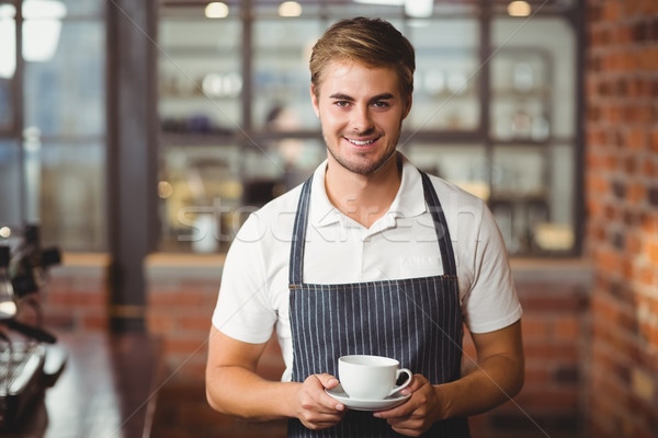 Handsome barista holding a cup of coffee Stock photo © wavebreak_media