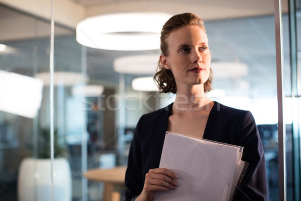 Businesswoman holdings documents while looking away Stock photo © wavebreak_media