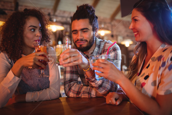 Young friends interacting with each other having drinks Stock photo © wavebreak_media
