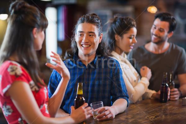 Happy friends interacting at bar counter Stock photo © wavebreak_media
