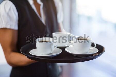 Mid section of waitress holding black coffee Stock photo © wavebreak_media