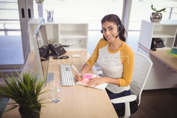 Vrouwelijke klantenservice vertegenwoordiger schrijven boek werken Stockfoto © wavebreak_media