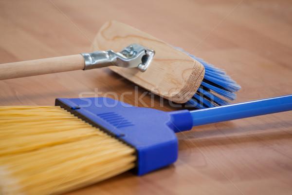 Two sweeping brooms on wooden floor Stock photo © wavebreak_media