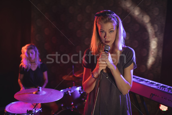 Confident female singer with drummer performing on illuminated stage in nightclub Stock photo © wavebreak_media