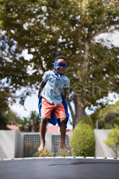 Boy in superhero costume jumping on trampoline Stock photo © wavebreak_media