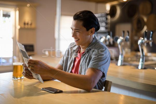Man reading newspaper in a restaurant Stock photo © wavebreak_media