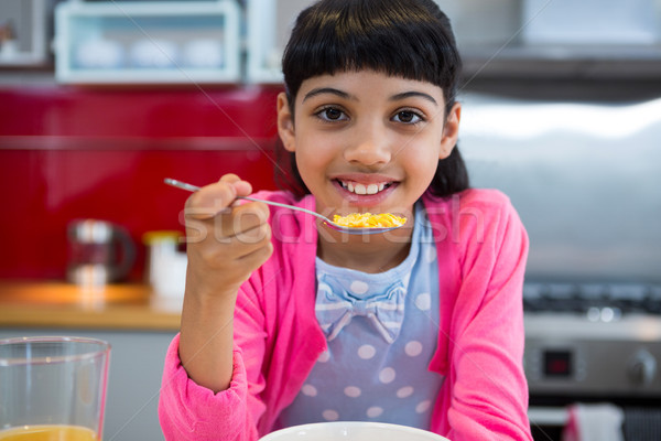 Girl holding breakfast cereal in spoon at home Stock photo © wavebreak_media