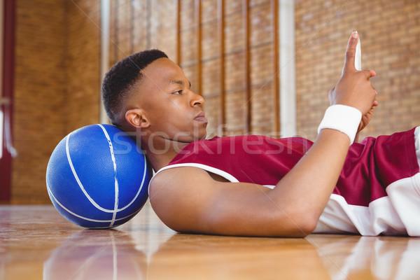 Oldalnézet férfi kosárlabdázó mobiltelefon padló bíróság Stock fotó © wavebreak_media