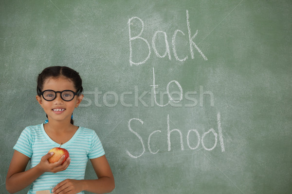 Young girl in spectacles hat holding apple Stock photo © wavebreak_media