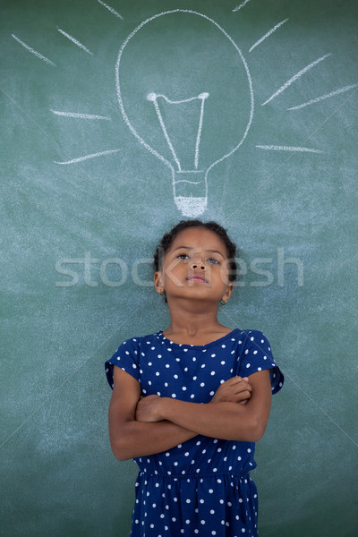 Girl with arms crossed standing by bulb drawing on wall Stock photo © wavebreak_media
