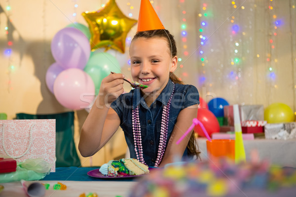 Girl eating cake during birthday party at home Stock photo © wavebreak_media