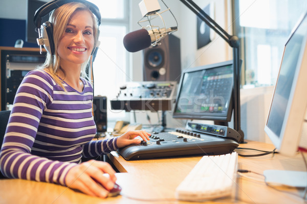 Portrait of female radio host using computer in studio Stock photo © wavebreak_media