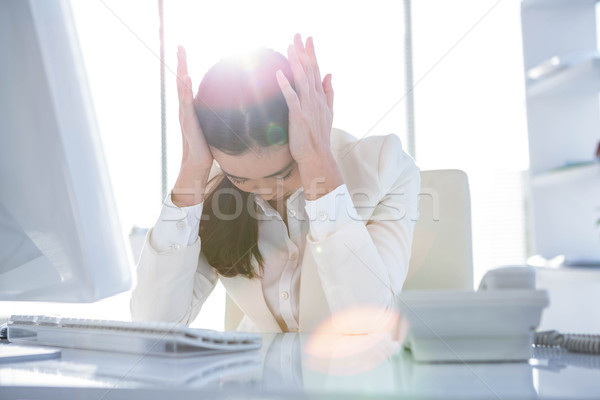 Stock photo: Stressed businesswoman working at her desk