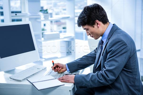 Focused businessman highlighting a document Stock photo © wavebreak_media