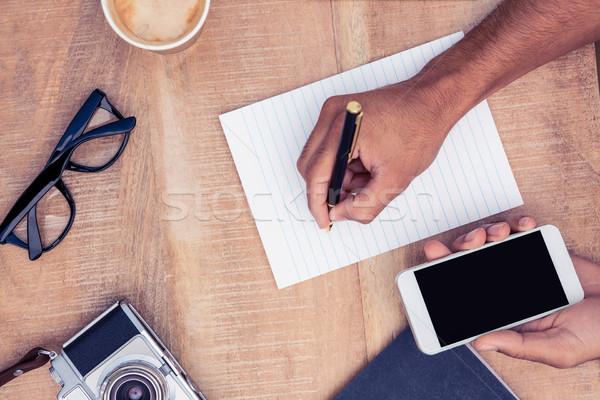Cropped image of businessman writing on notepad Stock photo © wavebreak_media