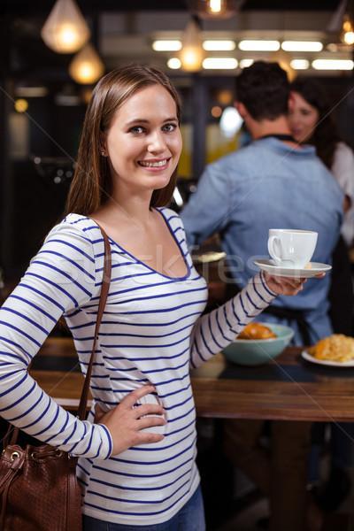 Smiling woman holding white cup Stock photo © wavebreak_media