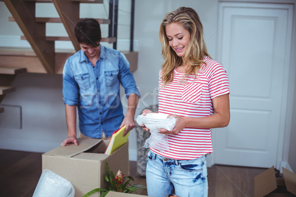 Smiling woman unpacking bowls from box with man  Stock photo © wavebreak_media