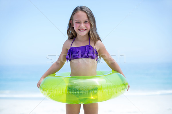 Cheerful girl with inflatable ring sea shore Stock photo © wavebreak_media