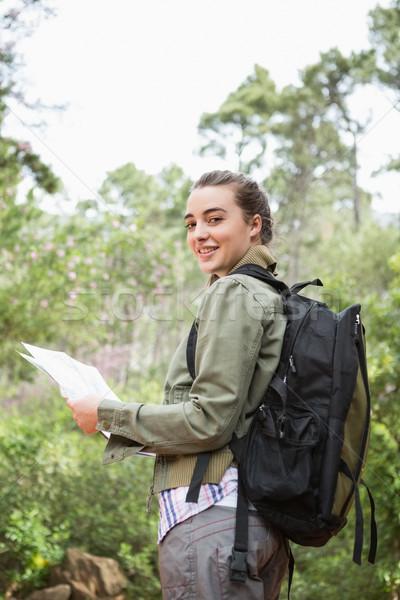 улыбающаяся женщина рюкзак карта женщину трава Сток-фото © wavebreak_media