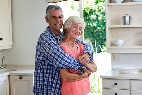 Smiling couple embracing in kitchen at home Stock photo © wavebreak_media