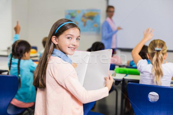 Portrait of schoolgirl standing with book in classroom Stock photo © wavebreak_media