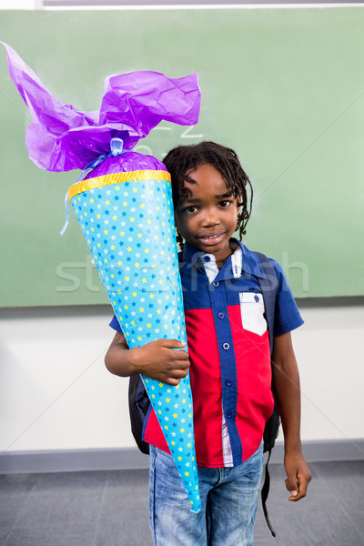 Boy holding gift against board in classroom Stock photo © wavebreak_media