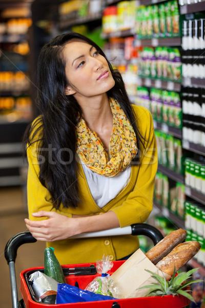 Mulher em pé carrinho de compras mercearia seção Foto stock © wavebreak_media