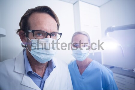 Doctor wearing protective glasses and surgical mask holding electronic chip Stock photo © wavebreak_media
