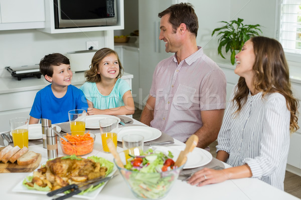 Smiling family interacting with each other while having lunch together Stock photo © wavebreak_media
