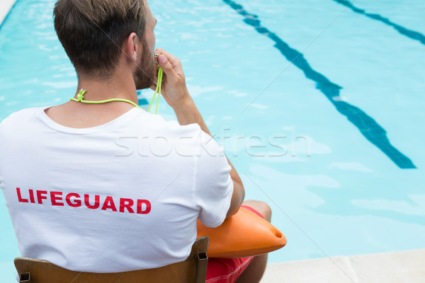 Lifeguard sitting on chair and blowing whistle at poolside Stock photo © wavebreak_media