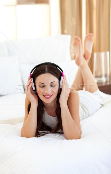 Peaceful woman lying down on bed listening music Stock photo © wavebreak_media