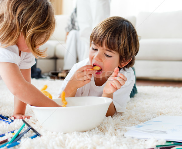 Cute children eating chips and drawing Stock photo © wavebreak_media