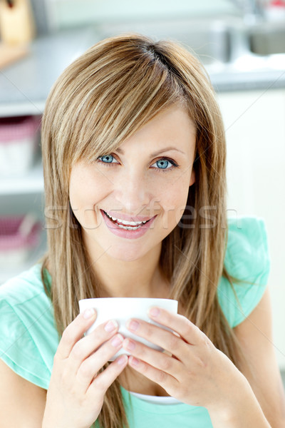 Delighted woman holding a cup of tea in the kitchen Stock photo © wavebreak_media