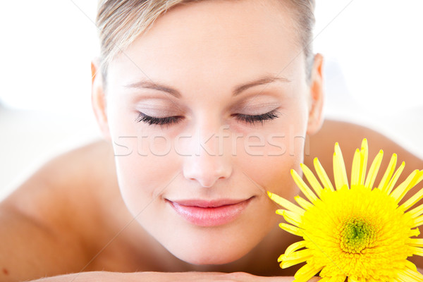 Close-up of a relaxed woman lying on a massage table with a flower in a health spa Stock photo © wavebreak_media