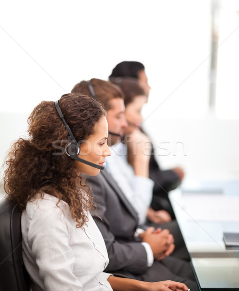 Four representatives on the phones with earpiece on sitting in their office Stock photo © wavebreak_media