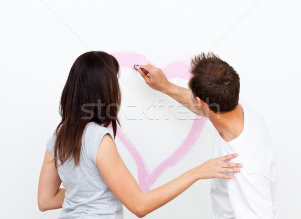 Rear view of a man drawing a heart for his girlfriend while renovating a room Stock photo © wavebreak_media