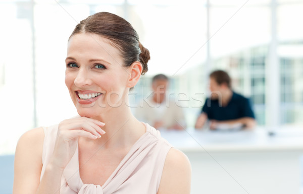 Smiling businesswoman looking at the camera while her coworkers are talking Stock photo © wavebreak_media