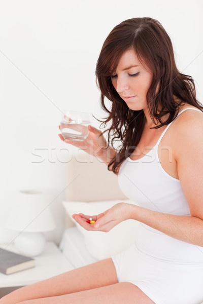 Beautiful brunette female taking some pills while sitting on a bed Stock photo © wavebreak_media