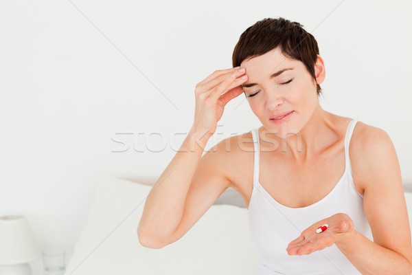 Cute brunette having a headache in her bedroom Stock photo © wavebreak_media