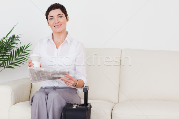 Short-haired smiling woman with a suitcase, a newspaper and a cup in a waiting room Stock photo © wavebreak_media