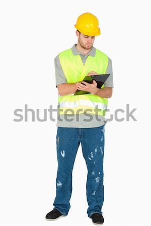 Young construction worker taking notes on his clipboard against a white background Stock photo © wavebreak_media