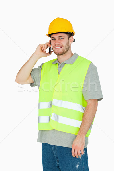 Smiling young construction worker on the mobile phone against a white background Stock photo © wavebreak_media