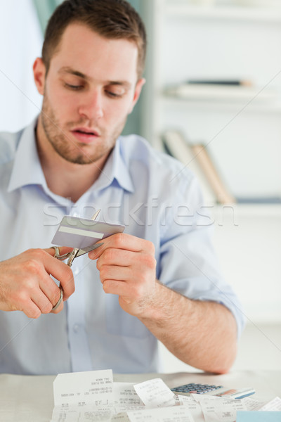 Stock photo: Young businessman getting rid of his credit card